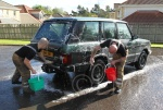 Firemen working hard with a sponge on the Range Rover