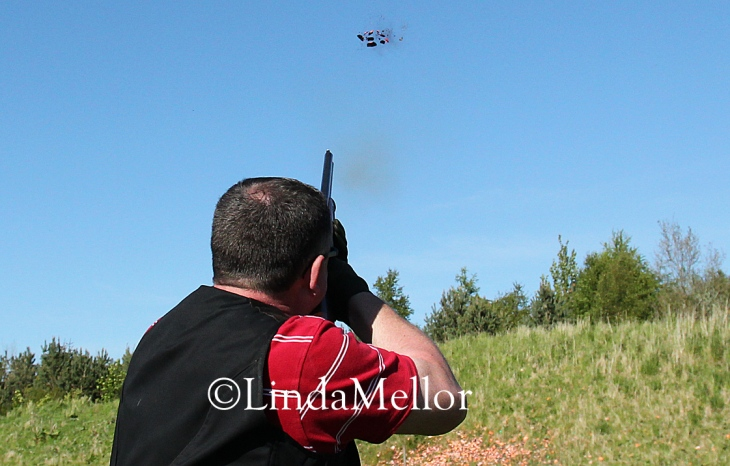Shooting clay targets on a sunny day against blue skies, Scottish Clay Shooting Centre