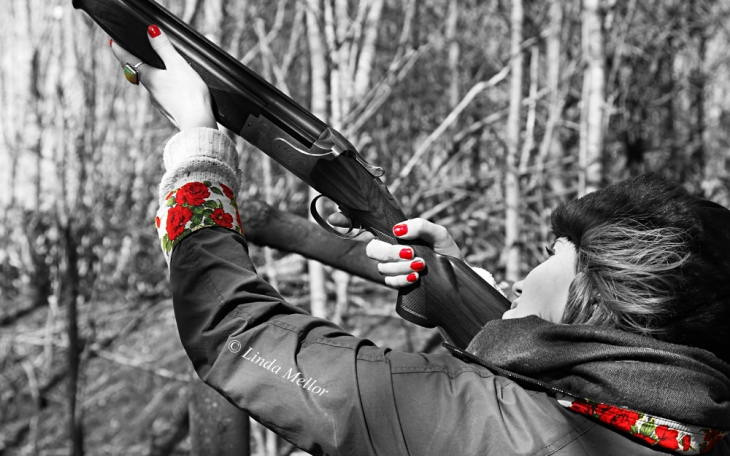 Lady shooting clays close-up. selective colour and black and white
