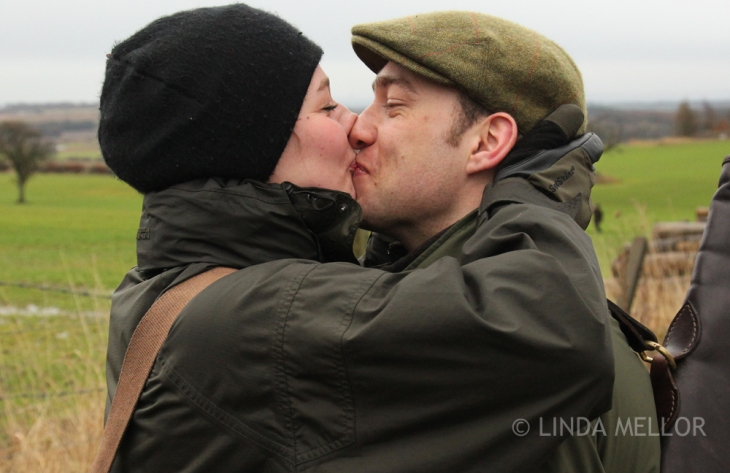 A countryside loving couple kissing on a shoot day.