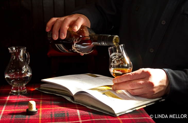 Pouring a dalmore whisky into a nosing glass on a tartan covered tablecloth